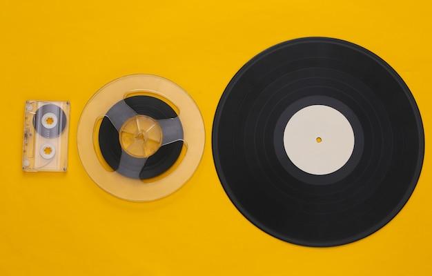 Postura plana retro. carretel de fita magnética de áudio, fita cassete e placa de vinil em amarelo