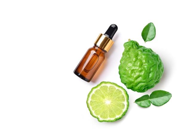 Postura plana (vista superior) de óleo essencial de bergamota com fruta bergamota em branco.