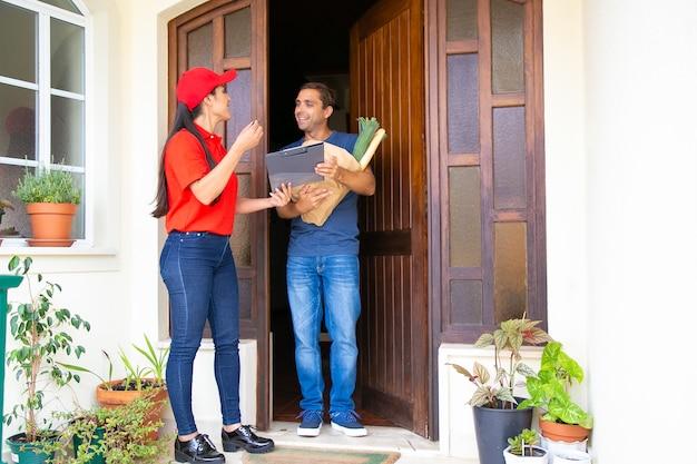 Postwoman latino segurando a área de transferência e entregando o pedido. entregadora feliz em uniforme vermelho, falando com o cliente e entregando legumes em saco de papel. serviço de entrega de comida e pós-conceito