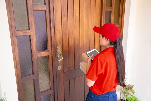 Postwoman profissional em frente a porta e segurando caixas de papelão. jovem mensageira em pé ao ar livre e segurando o tablet e pacotes ou pacotes. serviço de entrega e pós-conceito