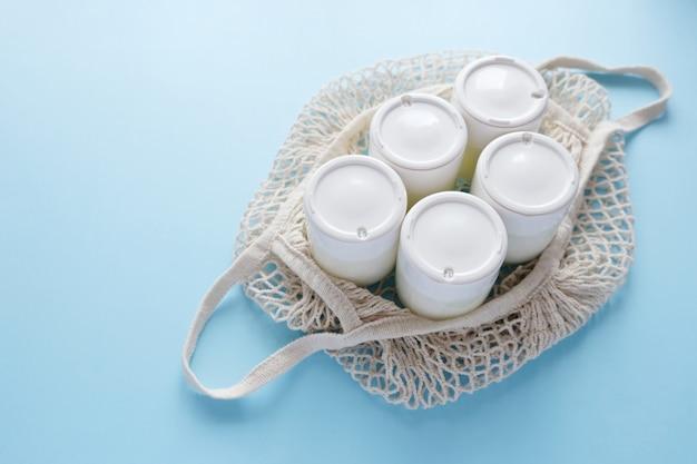 Pote caseiro de iogurte grego em potes de vidro em um saco de barbante sobre um fundo azul claro. foco seletivo, copie o espaço.