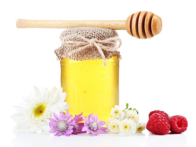 Pote cheio de delicioso mel fresco e flores silvestres, isolado no branco