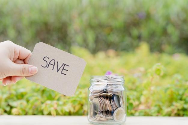 Pote cheio de moedas com salvar o papel da palavra sobre fundo natural verde turva. economizando dinheiro e o conceito de investimento.