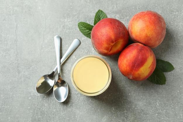 Pote com iogurte de pêssego, pêssegos e colheres em fundo cinza