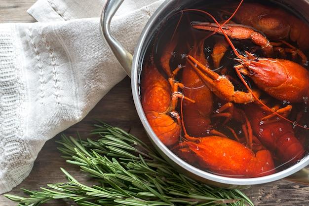 Pote com lagosta cozida na mesa de madeira