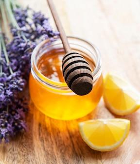 Pote com mel e flores frescas de lavanda em um fundo de madeira