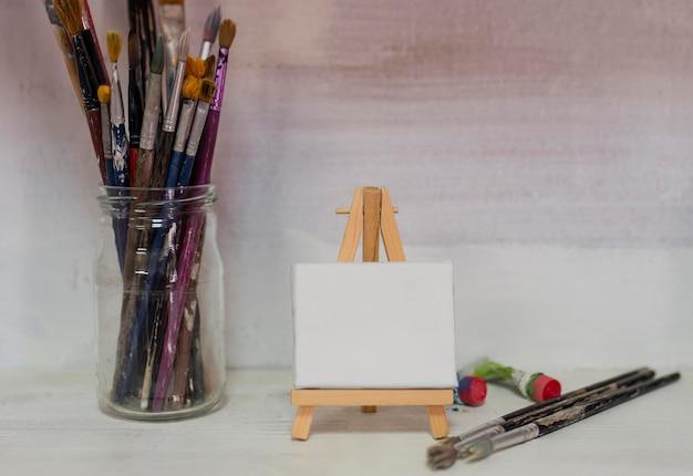 Pote com pincéis de pintura e tela