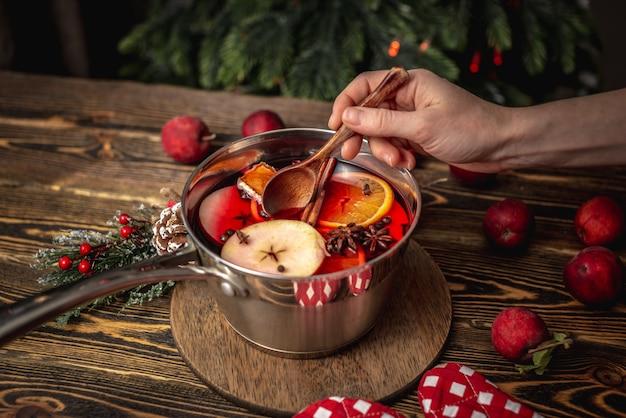 Pote com quentão em uma mesa de madeira com frutas e uma árvore de natal ao fundo. mão de mulher está mexendo a bebida com uma colher. conceito de atmosfera festiva acolhedora, clima de ano novo.