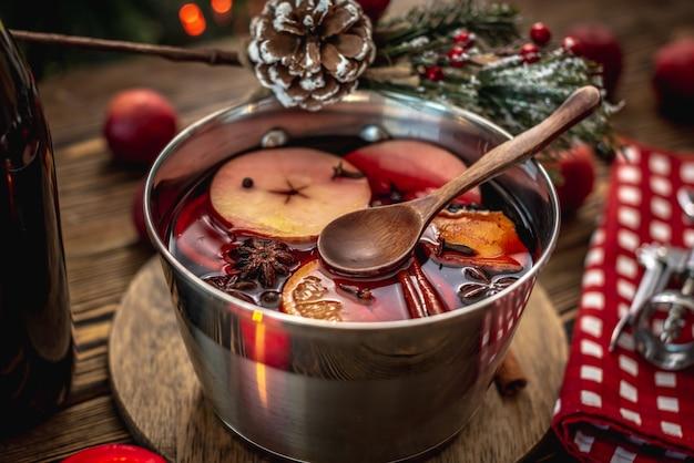 Pote com quentão quente perfumado picante em uma mesa de madeira rodeada por frutas e acessórios festivos. conceito de clima aconchegante de férias, clima de ano novo e natal