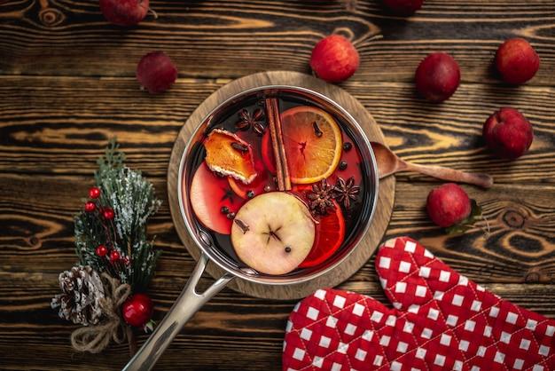 Pote com quentão quente perfumado picante em uma mesa de madeira rodeada por frutas e acessórios festivos. conceito de uma atmosfera acolhedora de férias, clima de ano novo e natal. vista do topo.