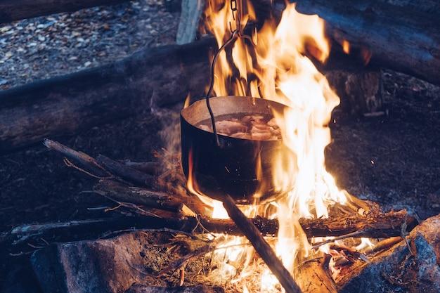 Pote de acampamento em chamas. alimentos fumegantes ao ar livre. estilo de vida selvagem cozinhando uma refeição deliciosa,