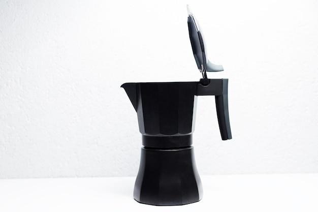 Pote de café preto moka, na superfície branca.