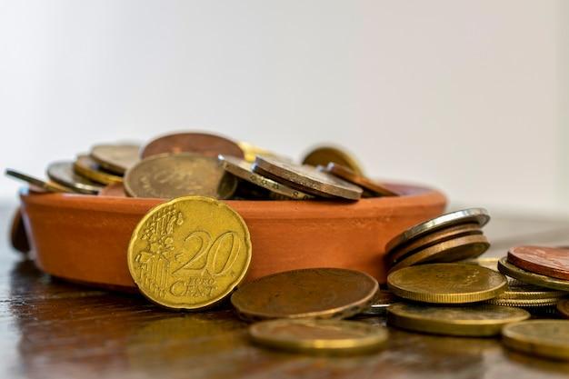 Pote de cerâmica com várias moedas, destacando-se 20 centavos de euro