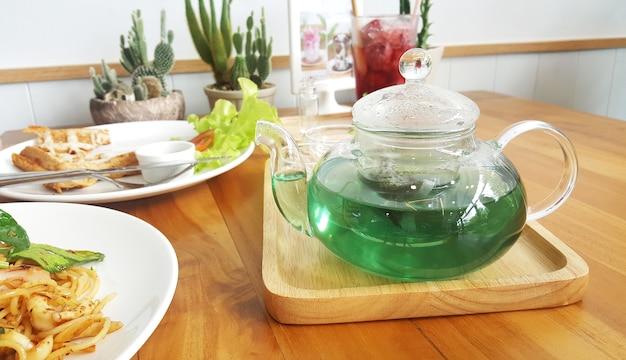 Pote de chá cristalino com chá de ervilha borboleta verde e limonada