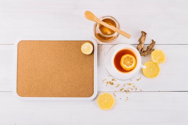 Pote de chá de mel e limão perto de gengibre no fundo de madeira
