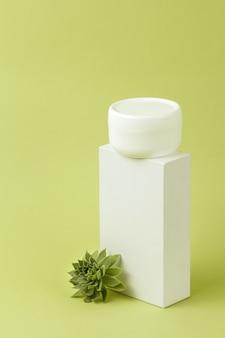 Pote de creme cosmético branco em suporte