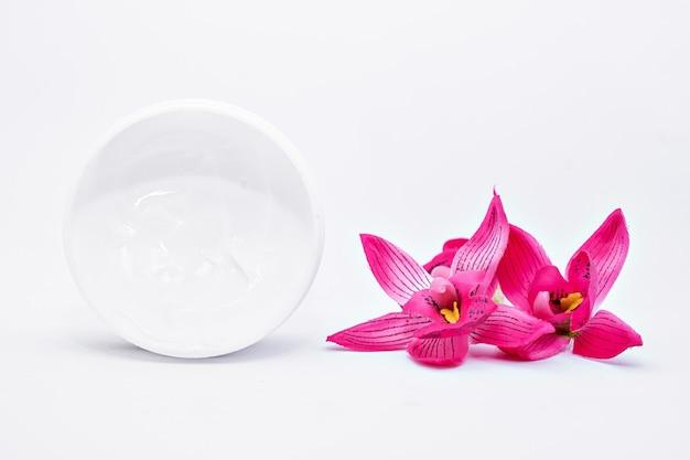 Pote de creme hidratante para o rosto com flor tropical rosa frangipani de orquídea na superfície branca