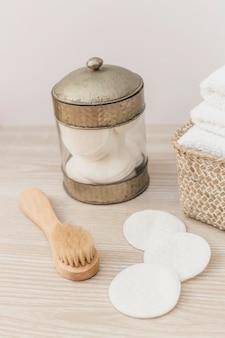 Pote de esponja; escova e toalhas no cesto na superfície de madeira