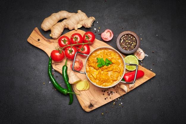 Pote de frango ao curry tradicional e temperos em uma tábua de madeira