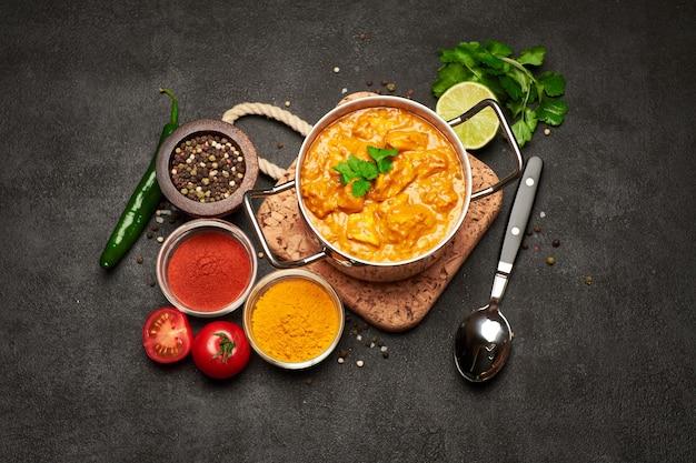Pote de frango ao curry tradicional e temperos em uma travessa de cortiça