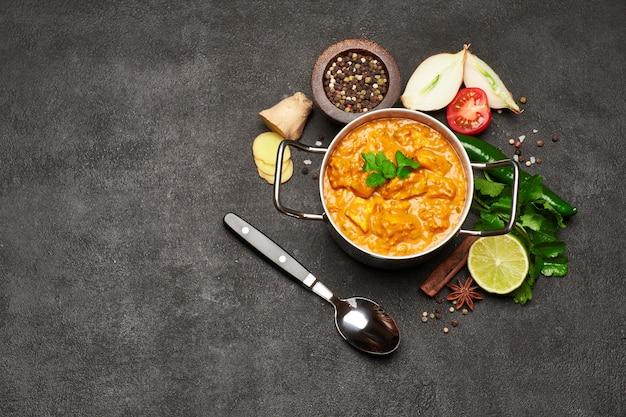Pote de frango ao curry tradicional e temperos na mesa escura