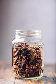Pote de frutas e sementes de anis estrelado na mesa de madeira