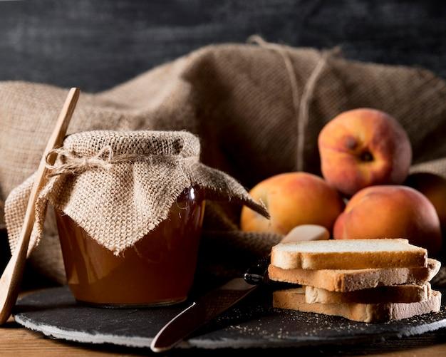Pote de geléia com pêssegos e pão