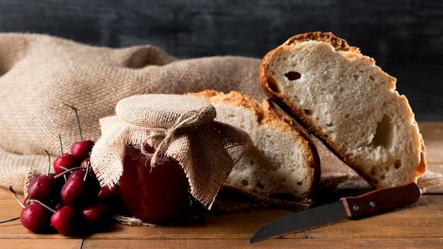 Pote de geléia de cereja com fatias de pão