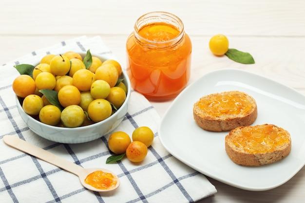 Pote de geléia doce, frutas ameixa e torradas