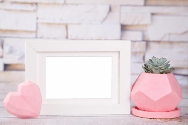 Pote de gesso branco moldura rosa, com planta suculenta