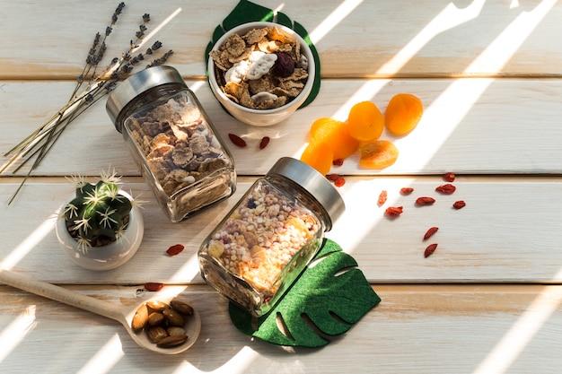 Pote de granola e flocos de milho perto de frutos secos em fundo de madeira