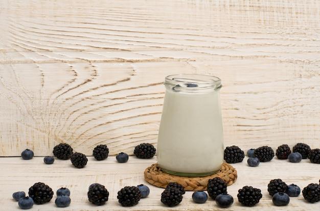 Pote de iogurte, amoras e mirtilos em uma mesa, madeira de fundo branco