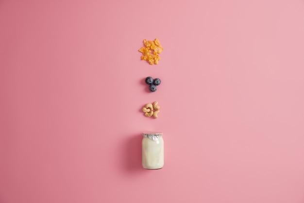 Pote de iogurte fresco, cereais, mirtilo e castanha de caju para preparar um delicioso mingau no café da manhã. ingrediente para uma refeição doce caseira ou sobremesa. conceito de lanche e dieta. fundo rosa.