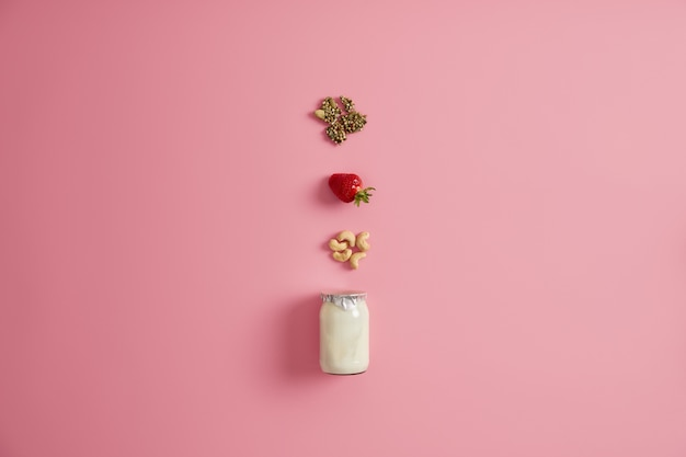 Pote de iogurte fresco e ingredientes como sementes de abóbora, morango maduro apetitoso, caju. sobremesa nutritiva caseira. conceito de dieta e superalimento. idéia saborosa para o café da manhã. vista de cima