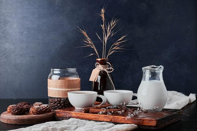Pote de leite com grãos de café e bombons de chocolate.
