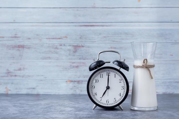Pote de leite com relógio clássico na mesa da cozinha, conceito de bebida da manhã.