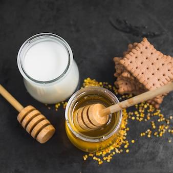 Pote de leite; pote de mel; pólens de abelha e pilha de biscoitos no pano de fundo texturizado