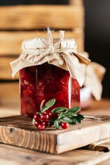 Pote de lingonberry caseiro e geléia de pêra com papel artesanal na tampa da mesa de madeira ao lado de lingonberries frescos. vertical
