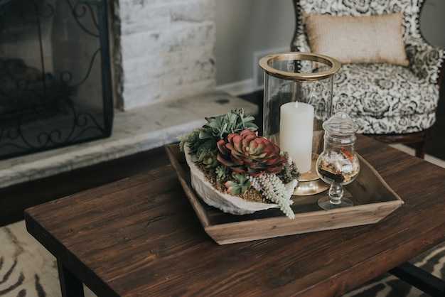 Pote de madeira em uma mesa de madeira com flores e velas perto de uma poltrona e uma lareira