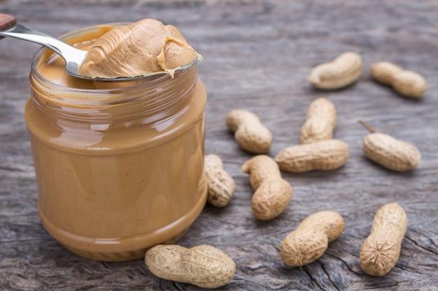 Pote de manteiga de amendoim com nozes. na textura de madeira.