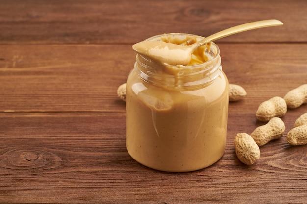 Pote de manteiga de amendoim e amendoim com casca na mesa de madeira marrom, vista lateral, nozes moídas frescas