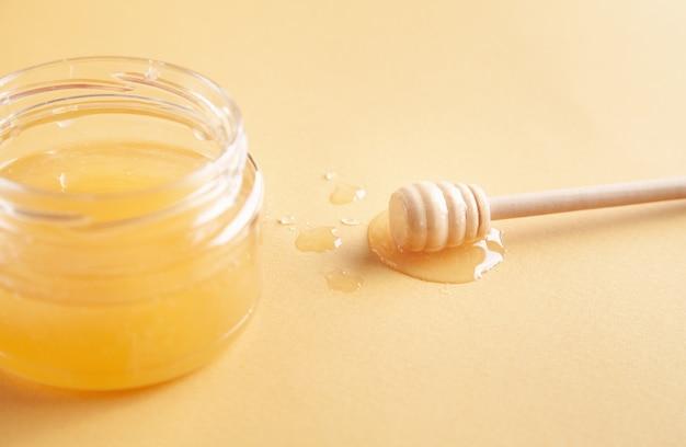 Pote de mel com concha em fundo amarelo.