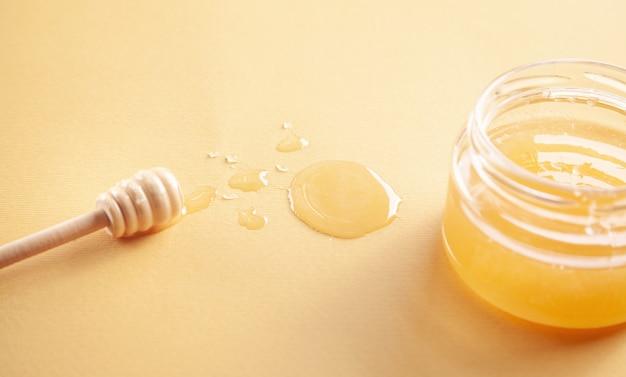 Pote de mel com concha em fundo amarelo. Foto Premium