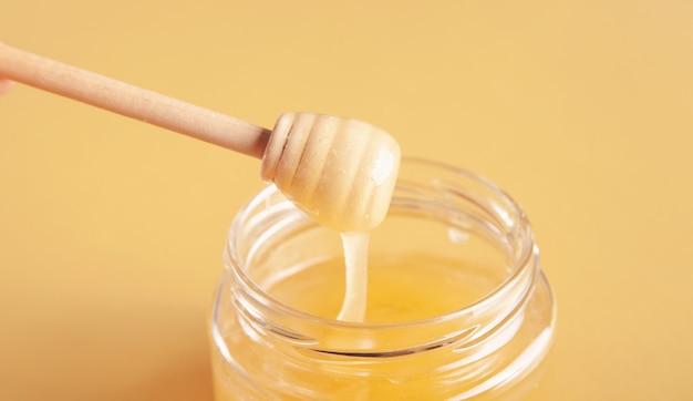 Pote de mel com concha na superfície amarela. Foto Premium