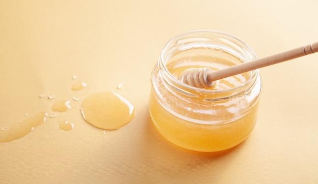 Pote de mel com concha na superfície amarela.