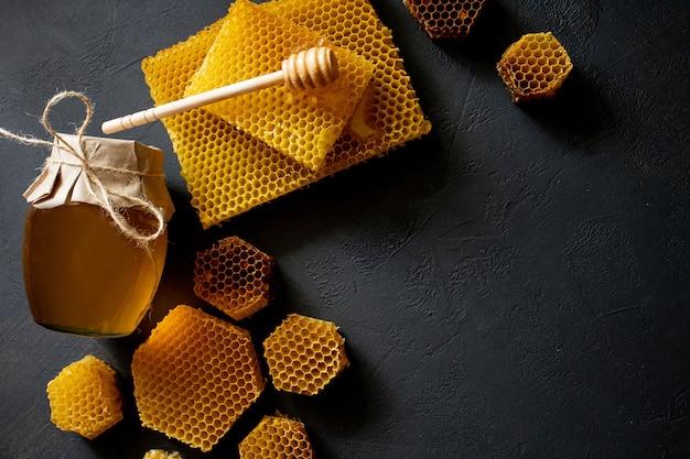 Pote de mel com favo de mel na mesa preta, vista superior. espaço para texto