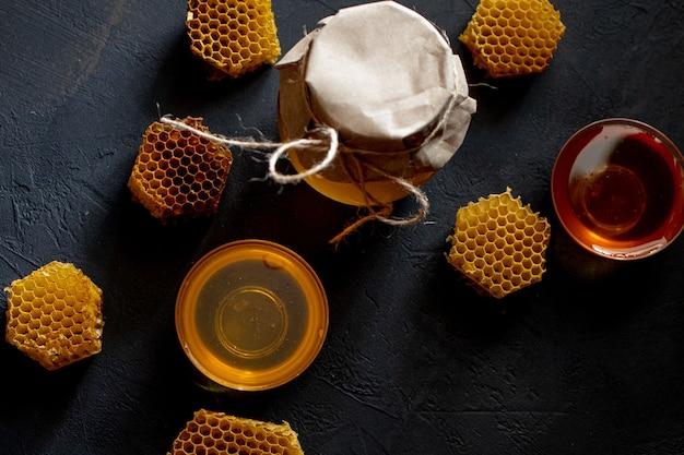 Pote de mel com favo de mel na mesa preta, vista superior. espaço para texto.