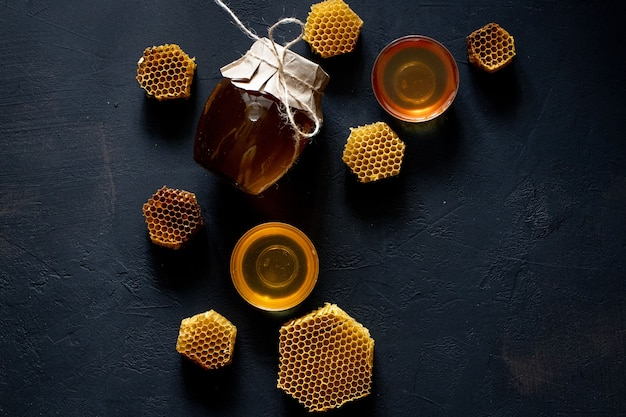 Pote de mel com favo de mel na mesa preta