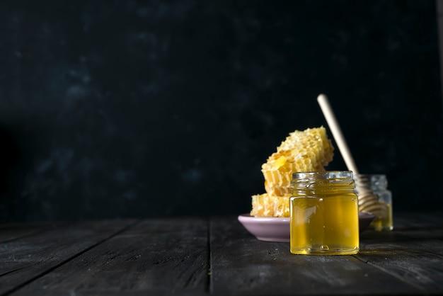 Pote de mel com uma vara de madeira drena o mel em um fundo escuro
