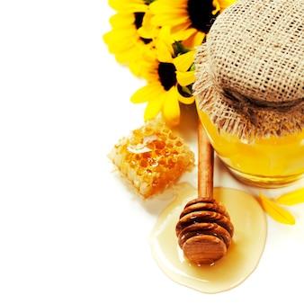 Pote de mel completo e palito de mel em branco, flores e favo de mel com copyspace